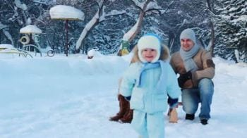 stock-footage-slow-motion-portrait-of-a-young-family-with-their-baby-in-a-winter-park-a-child-sits-on-a-sled.jpg