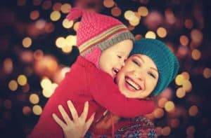 Mother and daughter hugging in front of Christmas lights