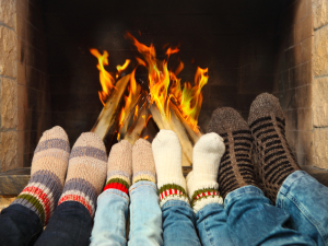Family of four warming up feet in front a fireplace in a Pigeon Forge group cabin