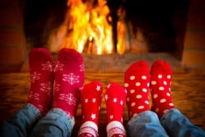 Family of three warming their feet by the fireplace on Christmas in Gatlinburg TN.