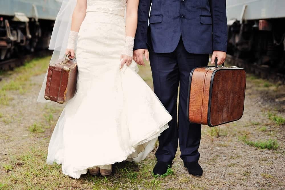 A bride and groom hold their packed bags ready for their honeymoon